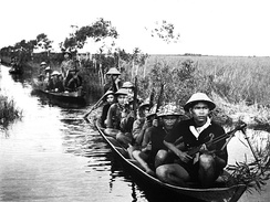 Việt Cộng guerrilla crossing a river in the Mekong Delta, 1966.