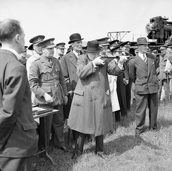 Churchill takes aim with a Sten sub-machine gun in June 1941. The man in the pin-striped suit and fedora to the right is his bodyguard, Walter H. Thompson.