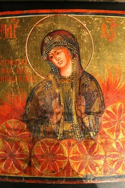 "The Fiery Chariot of the Word—19th-century Russian icon of the Theotokos as Ognyena Maria (""Fiery Mary""), fire goddess sister of Perun, and a glaring example of Slavic religious themes in Christianised fashion.[47] Belief in a mother goddess as receptacle of life, Mat Syra Zemlya (""Damp Mother Earth""), was preserved in Russian folk religion up to the 20th century, often disguised as the Virgin Mary of Christianity.[48] The fiery ""six-petaled roses"" that umbego the Ognyena are one of the variants of the whirling symbol of the supreme God (Rod).[20]"