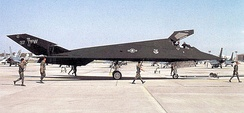 F-117A Nighthawk 85-0830 being towed at Tonopah after its return from Operation Desert Storm, 1991. Note the spotters, the armed security police with M-16s, and tow bar attached to the front landing gear.