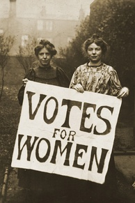 "Two woman carry a sign reading ""Votes for Women""."