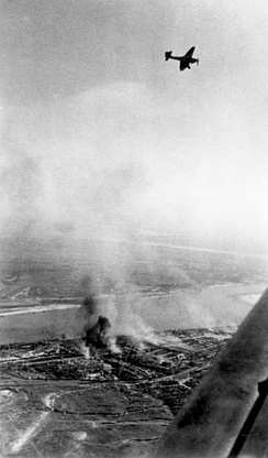 Junkers Ju 87 Stuka dive bombers above the burning city