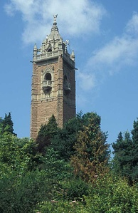 An ornate brick tower surrounded by trees. The tower has balconies and is surmounted by a pitched roof with an ornate figure at the apex.