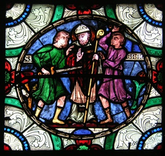 Stained glass image of three men. The central man is wearing a mitre and carrying a crozier. The man on the left is wielding a sword that is aimed right at the stomach of the central figure. The third man is throwing up his hands.