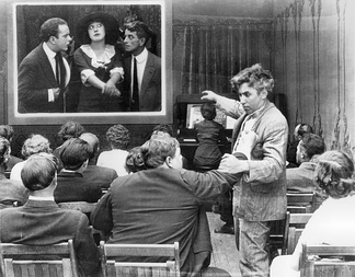 Movie theatre audience members Roscoe Arbuckle and Mack Sennett square off while watching Mabel Normand onscreen in Mabel's Dramatic Career (1913)