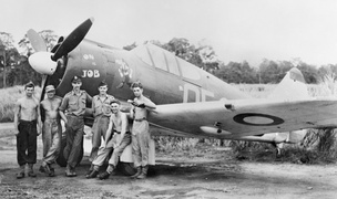 Six men in front of a single-engined military monoplane parked on a jungle airfield