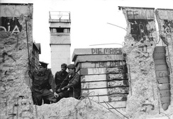 East German border-guards look through a hole in the Berlin Wall in 1990
