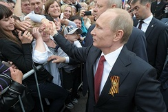Putin, with St. George ribbon, greets local residents during a visit to the Crimean city of Sevastopol on 9 May 2014