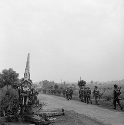 Infantry of 50th (Northumbrian) Division moving up past a knocked-out German 88mm gun near 'Joe's Bridge' over the Meuse-Escaut Canal in Belgium, 16 September 1944