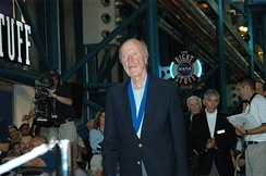 Cooper at an induction ceremony of the U.S. Astronaut Hall of Fame in 2004. Astronauts John Young and Gene Cernan stand behind him.