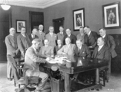Signing of the Dominion–Provincial Agreement on Old Age Pensions in 1928. (Seated, L–R): Peter Heenan, Thomas Donnelly, John Millar, W. R. Motherwell, William Lyon Mackenzie King, C. A. Dunning. (Standing, L–R): Fred Johnson, John Vallance, Ed Young, C. R. McIntosh, Robert McKenzie, Gordon Ross, A. F. Totzke, George McPhee, Malcolm McLean, William Bock.