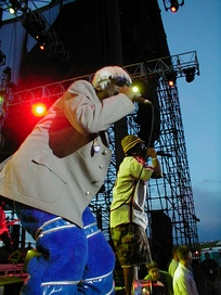 Two African-American men rap into microphones whilst on stage. One wears a blonde wig, a grey jacket and blue trousers, and the other wears a green checkered hat, a white shirt and khaki shorts.