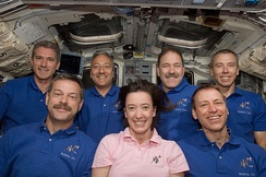 Crewmembers for the final Hubble Servicing Mission, STS-125 pose for a photo on the flight deck of Atlantis.