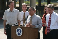 U.S. Representative Keith Ellison speaking at the site of the I-35W Mississippi River Bridge collapse in Minneapolis. He is flanked by Governor Pawlenty on the picture's left. To right: Mayor R. T. Rybak, Secretary of Transportation Mary Peters behind Ellison, Betty McCollum, and Senator Norm Coleman