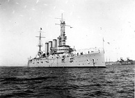 An armored cruiser anchored, with a navy jack flying from the jackstaff