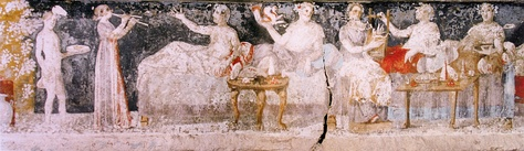 A banquet scene from a Macedonian tomb of Agios Athanasios, Thessaloniki, 4th century BC; shown are six men reclining on couches, with food arranged on nearby tables, a male servant in attendance, and female musicians providing entertainment.[306]