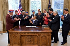 President Obama with surviving veterans of the 100th after signing S.1055, a bill to grant the unit the Congressional Gold Medal.