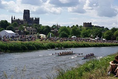 Durham Cathedral and castle as seen from the river bank whilst a boat race takes place between University College, Durham and Newcastle University