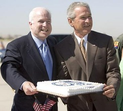 President George W. Bush presenting birthday cake to Senator McCain. Luke Air Force Base, August 29, 2005.