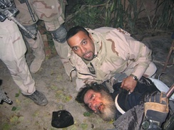 Saddam Hussein being pulled from his hideaway in Operation Red Dawn, 13 December 2003.