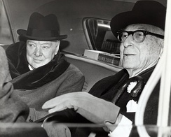 Winston Churchill and Bernard Baruch converse in the back seat of a car in front of Baruch's home.