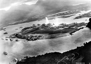 Photograph from a Japanese plane of Battleship Row at the beginning of the attack. The explosion in the center is a torpedo strike on the USS West Virginia. Two attacking Japanese planes can be seen: one over the USS Neosho and one over the Naval Yard.