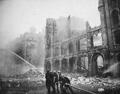 Firefighters tackling a blaze amongst ruined buildings after an air raid on London