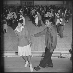 """Tubbie"" Kunimatsu and Laverne Kurahara demonstrate some intricate jitterbug steps, during a school dance held in the high school gymnasium, November 1943."