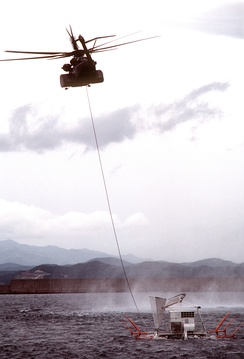An MH-53E from HM-15 tows a minesweeping sled while conducting simulated mine clearing operations
