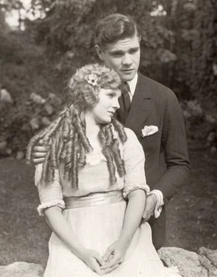 Mary Miles Minter (playing Anne Shirley) snuggles with Paul Kelly (Gilbert Blythe) in a scene still for the 1919 silent film Anne of Green Gables