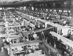Mechanized P-38 assembly lines in Burbank, California. Planes start at the back of the building on the far right (without wings, so that section of the line is narrower). When they reach the end of that line, they shift to the center line, gain wings, and move backward down this line. Upon reaching the end, they are then shifted to the line at the left, and progress forward to the end of the line.[34]