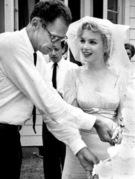 Cropped photo of Monroe and Miller cutting the cake at their wedding. Her veil is lifted from her face and he is wearing a white shirt with a dark tie.