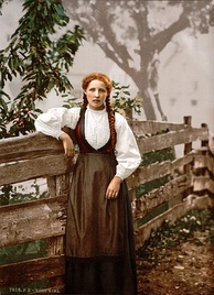 A girl with auburn hair in pigtails poses next to a rude wooden fence. She wears a white ruffled shirt and a long brown dress.