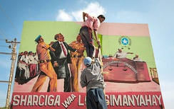 "A billboard mural saying ""Before the law, all people are equal"" fixed into place by a cooperative of artists along the approach road to Mogadishu International Airport"