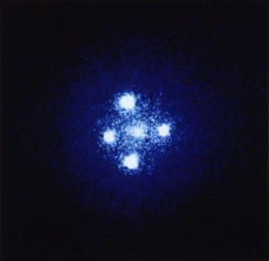 In the formation known as Einstein's Cross, four images of the same distant quasar appear around a foreground galaxy due to strong gravitational lensing.