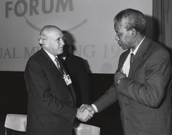 World Economic Forum, 1992: F. W. de Klerk (the last white minority president of South Africa) shakes hands with Nelson Mandela (who later became the first freely elected black president).
