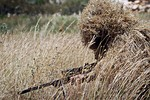 Sniper in a Ghillie suit with plant materials