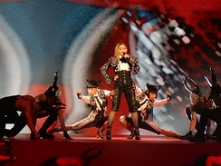 Madonna standing in the middle of a stage. Her dancers flank her near the stage floor.