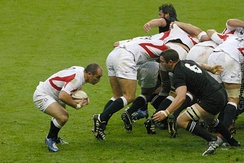 New Zealand blindside flanker Reuben Thorne detaches from a scrum to tackle England's Shaun Perry.