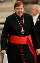 George Cardinal Pell wearing the ordinary dress of a cardinal: black cassock with scarlet (red) piping and buttons, scarlet fascia (sash), pectoral cross on a chain, and a scarlet zucchetto.