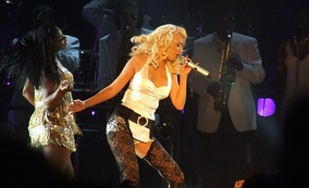 "Aguilera performing ""Still Dirrty"" in a white bodysuit and black lace thigh-highs"