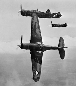 "In the vicinity of Moore Field, Texas. The lead ship in a formation of P-40s is peeling off for the ""attack"" in a practice flight at the US Army Air Forces advanced flying school. Selected aviation cadets were given transition training in these fighters before receiving their pilot's wings, 1943."