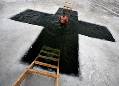 An ice hole is cut in the form of a cross in Russia to celebrate the Epiphany