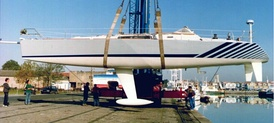 The hull of a racing yacht being lifted from the water for maintenance