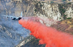 C-130E Hercules cargo aircraft from the 146th Airlift Wing, California, rigged with a Modular Airborne Fire Fighting System (MAFFS) makes a Phoschek fire retardant drop on the Simi Fire in Southern California, 28 October 2003.