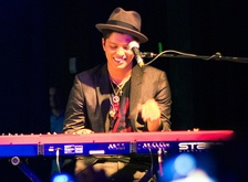 Bruno Mars playing the keyboard in a concert in Houston