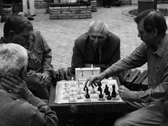 Photo shows two men playing chess while two more look on.