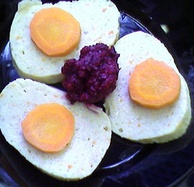 Gefilte fish with carrot slices and chrain