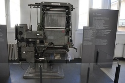 "An Intertype Fotosetter, one of the most popular ""first-generation"" mass-market phototypesetting machines. The system is heavily based on hot metal typesetting technology, with the metal casting machinery replaced with photographic film, a light system and glass pictures of characters."