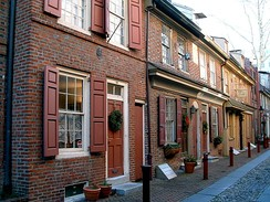 "Elfreth's Alley in Philadelphia features Federal-style homes and is referred to as ""Our nation's oldest residential street,"" dating to 1702[1]"
